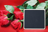 Red roses and black board for congratulations — Stok fotoğraf