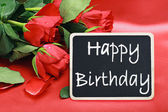Roses and a blackboard with congratulations on his birthday — Foto Stock
