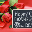 Roses and a blackboard with congratulations from mothers day — Stock Photo
