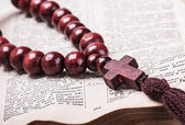 Rosary with a wooden cross lying on open Bible — Stock Photo