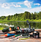 Fishing tackle on a pontoon on the background of the lake  — ストック写真