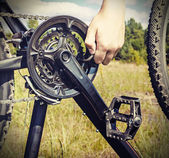 Hand with key repairs bike — Stock Photo