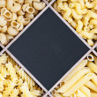 Pasta assortment and blackboard for text — Stock Photo