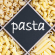 Pasta assortment and blackboard with text — Stock Photo