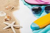 Beach gear lie on the sand with shells  — Stock Photo