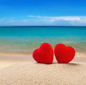 Two red hearts in the sand   — Stock Photo