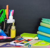 School stationery laid on a background of chalkboard  — Stock Photo