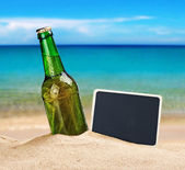 Beer bottle in the sand — Stock Photo