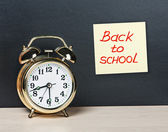 Alarm clock and sticker with text back to school on the chalkboa — Stock Photo