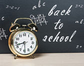 Alarm clock on a background of chalkboard — Stock Photo