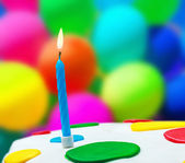 Lighted candle on a birthday cake — Stock Photo
