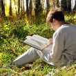 Boy reading outdoor — Stock Photo