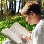 Boy reading outdoor — Stock Photo