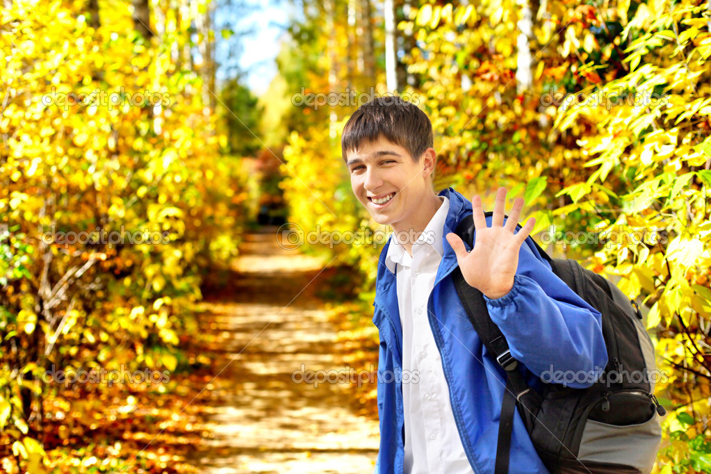 Young man wave goodbye in the autumn park avenue — Stock Photo #12421705