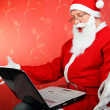 Santa claus with laptop — Stock Photo