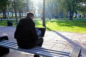 Homem com laptop no parque — Foto Stock