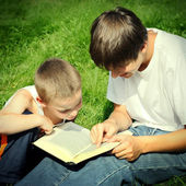 Teenager and Kid with a Book — Stock Photo