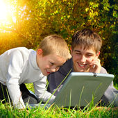 Brothers with Laptop outdoor — Stock Photo