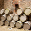 Wooden barrels against a vintage brick wall — Stock Photo