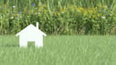 Symbol of house on grass field — Stock Photo