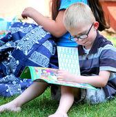 Boy reading outside. — Stock Photo