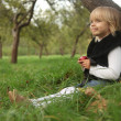 Cute little 4-year girl with apple sitting under a tree in park — Stock Photo