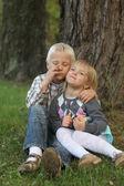 Zwei Kinder sitzen unter dem Baum — Stockfoto