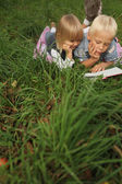 Blond 6-year-old boy and 4-year-old girl reading a book lying on — Stock Photo
