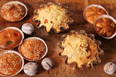 Hand-made muffins and colored white walnut on the background of — Stock Photo