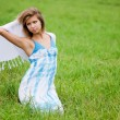 The beautiful woman in a blue dress in the field - Stock Photo