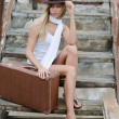 The beautiful woman with a suitcase on an old ladder - Foto Stock