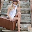 The beautiful woman with a suitcase on an old ladder — Stock Photo