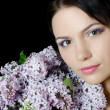 Beautiful woman with spring flowers of a lilac. Skincare - Stock Photo