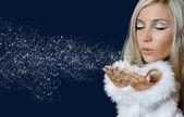 Attracive girl in santa cloth blowing snow from hands — Stock Photo