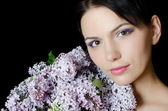 Beautiful woman with spring flowers of a lilac. Skincare — Stock Photo