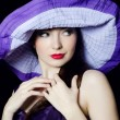 Portrait of the beautiful elegant woman in a lilac hat — Stock Photo #13808347