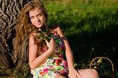 La chica se sienta en una hierba con una canasta en una puesta de sol — Foto de Stock