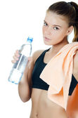 The sports girl with a towel and a water bottle — Stock Photo