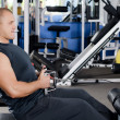 Man on training apparatus in club — Stockfoto