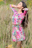 The beautiful woman in a dress in the field — Stockfoto