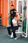 Woman on training apparatus in club — Stockfoto