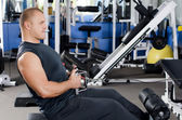 Man on training apparatus in club — Stock Photo