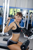 Woman on training apparatus in club — Foto Stock
