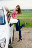 The beautiful girl stands near to white car — Stock Photo