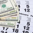 Banknotes of dollars on calendar sheets — Stock Photo #16907817