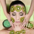 Stock Photo: Girl with mask from kiwi on face