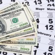 Banknotes of dollars on calendar sheets — Stock Photo