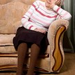 Portrait of the old woman on a sofa — Stock Photo #19989395
