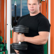 Man with dumbbells in sports club — Stock Photo