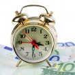 图库照片: Alarm clock for euro banknotes isolated